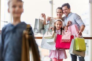 Glückliche Familie zeigt ihre Einkaufstüten