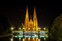 Blick auf die historische Kirche Saint Paul am Fluss Ill in Straßburg bei Nacht, Elsass, Frankreich