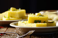 Polenta with butter and greens on clay dish on wooden rustic table