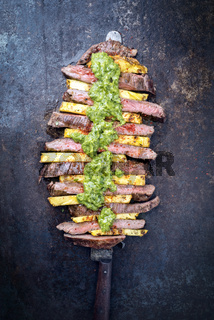 Traditional Barbecue dry aged wagyu flank steak with pineapples and chimichurri sauce as top view on a knife on an old metal sheet with copy space