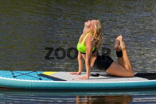 Dutch woman practicing yoga posture on SUP