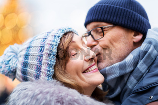 close up of happy senior couple kissing in winter