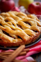Homemade pastry apple pie with bakery products on dark wooden kitchen table