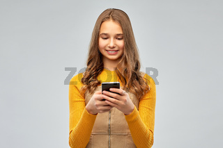 smiling teenage girl using smartphone