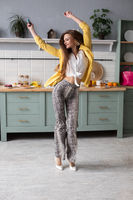 Stylish happy brunette girl in snake printed trousers dancing in the kitchen.