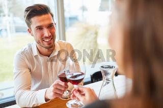 Verliebtes Paar beim Anstoßen mit einem Glas Wein