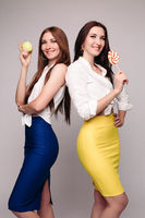 Two beautiful brunette young ladies with candy and apple.