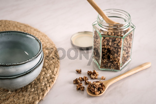 Homemade healthy and nutritious breakfast granola in a glass jar and on wood spoon with blue ceramic bowls on marble kitchen table in fresh morning light