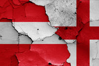 flags of Austria and England painted on cracked wall