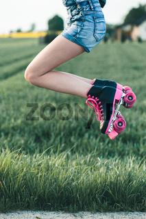 Teenage girl having fun rollerskating, jumping, spending time outdoors