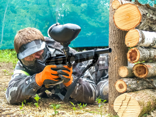 A paintball player who is ready to shoot from hiding. Lying on the ground and shooting.