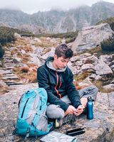 Boy resting on a rock and charging a mobile phone during trip in the Tatra Mountains