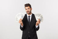 Portrait of a satisfied young businessman holding bunch of money banknotes isolated over white background.
