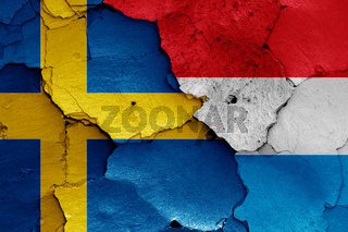 flags of Sweden and Luxembourg painted on cracked wall