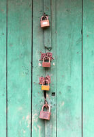 Wooden door locked by 4 different padlocks