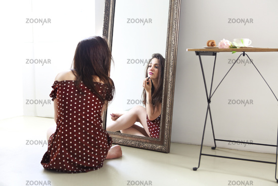 Beautiful woman in polka dots dress applying lipstick and looking at mirror