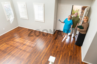 Female Real Estate Agent Showing Senior Adult Couple A New Home