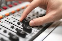Male hand on control Fader on console. Sound recording studio mixing desk with engineer or music producer.