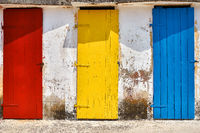 Few old wooden colorful doors on shabby light wall background