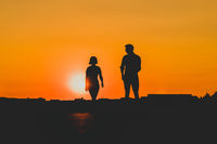 silhouette of young man and woman looking at each other on sunset sky background