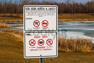 Warning signs around storm drainage pond
