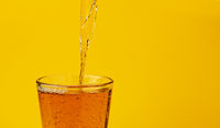 Apple juice pouring into glass, isolated on yellow background