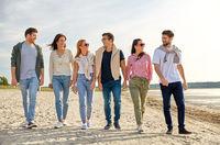 happy friends walking along summer beach