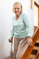 Elderly woman at home using a walking cane to get down the stairs