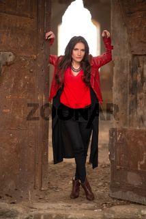 Fashion concept portrait of a gorgeous young woman in red leather jacket and black skirt outfit, sitting in a door of an old abandoned building and looking at the camera. Retouched, vibrant colors
