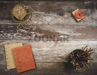 Rustic old vintage wood table with burning incense, incense sticks, natural twine and two small handmade books, with background copyspace - Concept of relaxing mindfulness, unplugging and creative inspiration