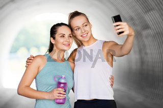 sporty women taking selfie by smartphone outdoors