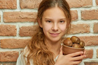 Girl teenager with long hair holding plate with kiwi
