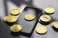 Golden litecoin coin on a smartphone with a lot of bitcoins coins on a table. Virtual cryptocurrency concept. Mining of bitcoins online bussiness. Bitcoins trading.