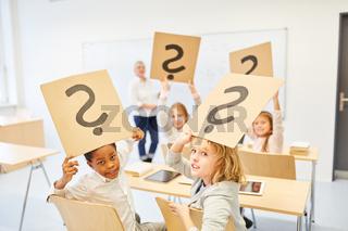 Kinder in der Grundschule halten Fragezeichen