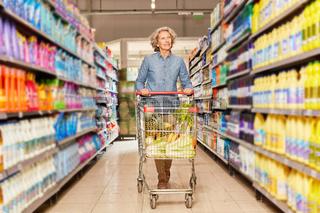 Seniorin mit vollem Warenkorb im Supermarkt
