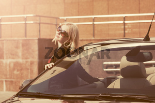 Young fashion woman in sunglasses leaning on her convertible car