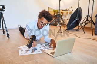 Fotograf bei der Bildauswahl am Laptop Computer