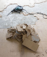 Construction concept - Jackhammer, removing chipboard from the floor