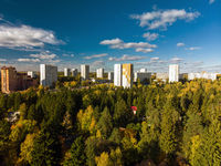 high-rise city houses surrounded by autumn forest in Russia in Moscow