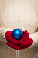 Woman Wearing Seasonal Red Mittens Holding Blue Christmas Ornament