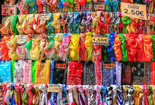 Rows of colorful scarves hanging at portuguese market