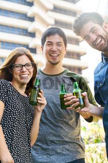 Gruppe Studenten feiert mit einer Flasche Bier
