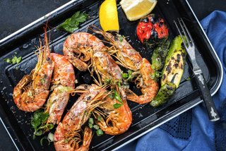 Traditional fried black tiger prawn with vegetable and lemon as top view in a black skillet