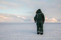 Man with a rifle looks out on the horizon in arctic landscape at Svalbard