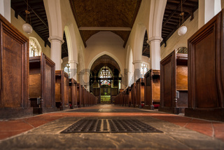 Along a church isle flanked by old wooden church pews leading to the alter and grand stained glass window.