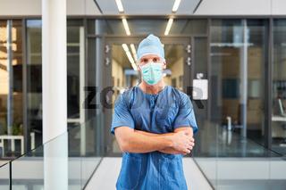 Junger Mann als Chirurg mit verschränkten Armen