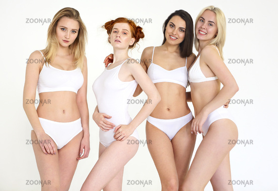 Cheerful young multiethnic women in white lingerie together