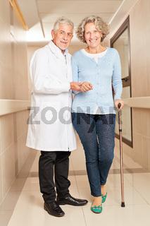 Arzt stützt Senior Frau mit Krücke