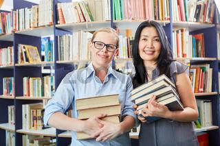 Studentin und Bibliothekarin mit Bücher Stapel