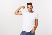 Handsome fit young funny bearded man pointing to his bicep and smiling on white background